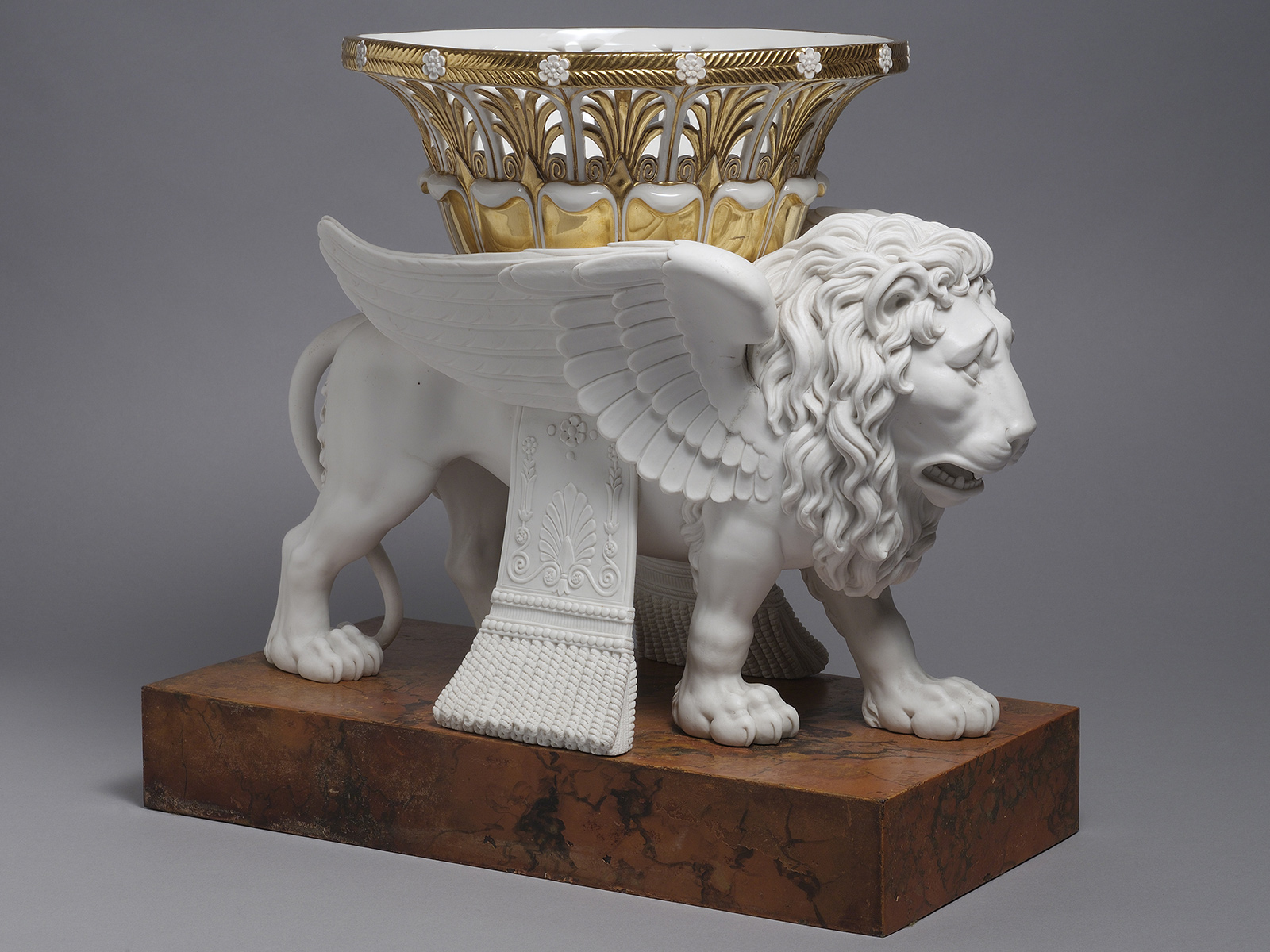 Pair Sèvres Biscuit models of Lions supporting gilt-white reticulated Baskets